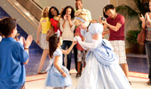 A group of Guests cheer and photograph a young princess as she meets Cinderella.