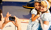 Cinderella and a young girl pose for a photo.
