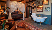 Master bedroom with netted bed, claw-foot tub and luxurious leather easy chairs.