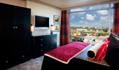 A flat-screen TV and large, black wardrobe and drawers face the plush bed.