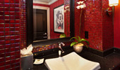 A square sink sits beneath a mirror in a red-tiled bathroom.