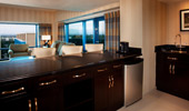A wet bar, a refrigerator, dark wood cabinets and a view of Disneyland Resort from the living area of a 2-Bedroom Suite.