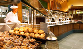 A long shot of the buffet with many croissants, sweet breads and muffins.