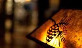 Close up on a lit lamp shade with an an acorn detail