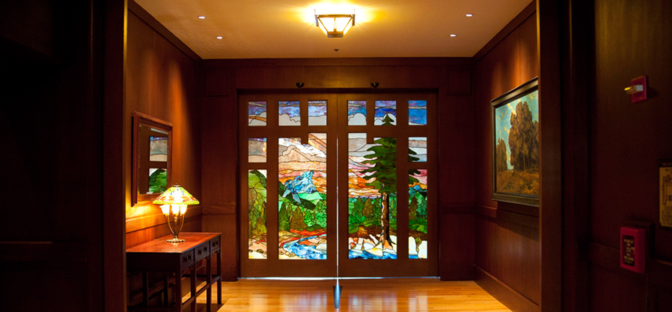 Stained glass doors at the end of the hallway show a scene with a bright blue sky, lush evergreen trees and a sparkling creek.