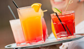 Close up of a server's tray with 5 colorful drinks