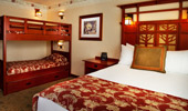 Wide shot of room with queen-size bed and bunk beds