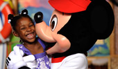 Mickey Mouse gives a girl a kiss on the cheek.
