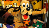 Pluto poses for a silly picture with 2 young Guests.