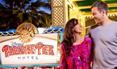 A couple stand by the sign: Disney's Paradise Pier Hotel