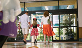 A mom and dad hold hands with their young girl who is dressed as Minnie Mouse.