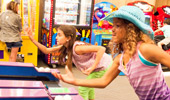 2 girls play a game of skee ball.