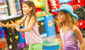2 girls play an arcade game.